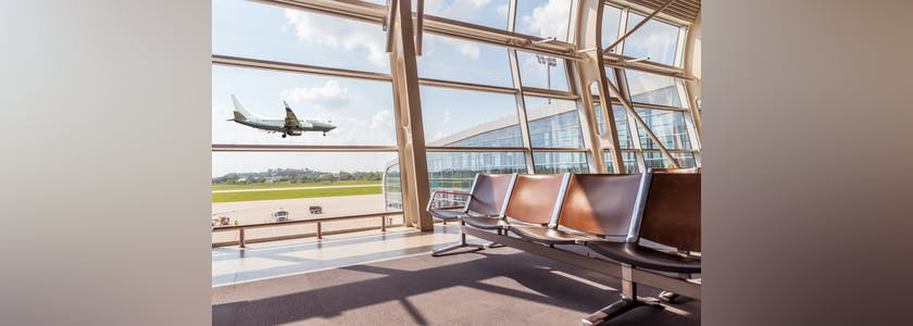 View from the airport lounge to landing aircraft, Car airfield maintenance at airport apron. Airplane travel concept