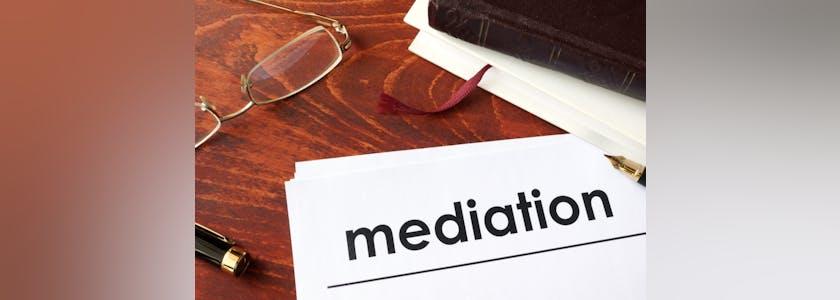 Une feuille intitulée Médiation posée sur un bureau avec un carnet et des lunettes