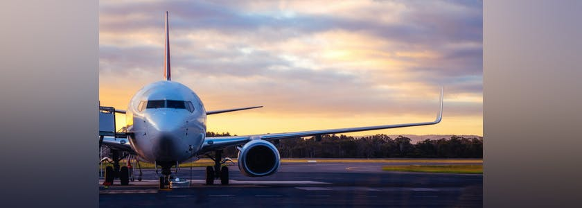 Sunset view of airplane on airport runway under dramatic sky in Hobart,Tasmania, Australia. Aviation technology and world travel concept.