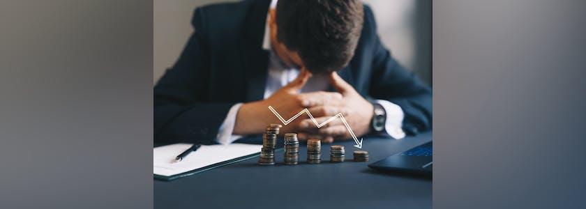 Photo d'un homme devant un tas de pièces et une courbe descendante illustrant une entreprise en difficulté
