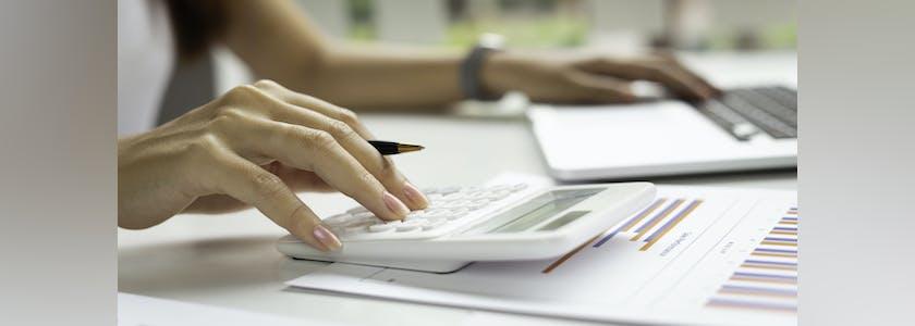 Mains de femme tapant sur une calculatrice et un ordinateur portable