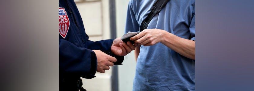 Mains d'un homme qui tend ses papiers d'identité à un policier