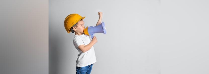 Enfant avec un casque de chantier et un mégaphone, le poing levé