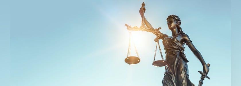 Photo d'une statue tenant la balance de la justice. Figuration du concept du visage de la justice, des libertés publiques