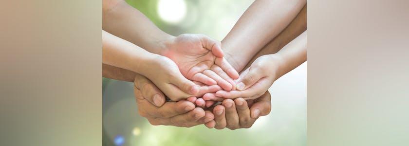 Mains d'enfant au dessus des mains de ses parents, paume vers le ciel