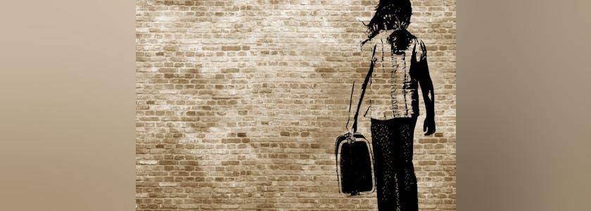 Graffiti sur un mur de brique représentant une femme avec une valise. Image conceptuelle de l'immigration