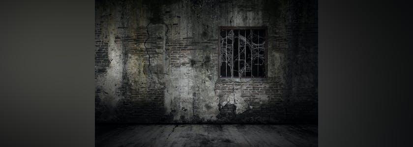 mur et grille d'une prison délabrée