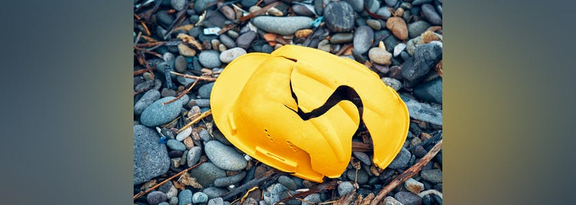 Cracked work helmet on the floor covered with pebble stones. Concept of work accident.