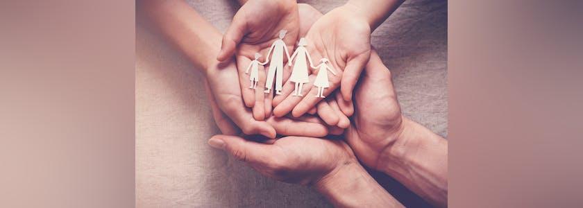Famille en papier dans le creux des mainss