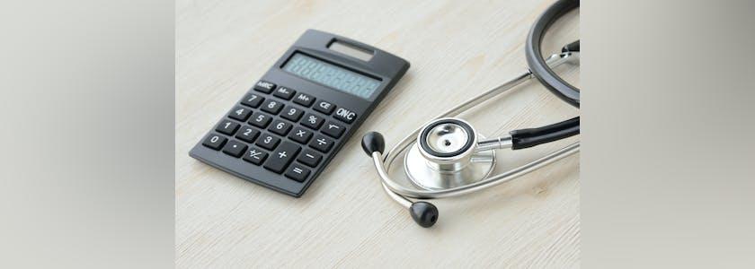 Calculatrice et stéthoscope posés sur une table, image conceptuelle dela responsabilité médicale