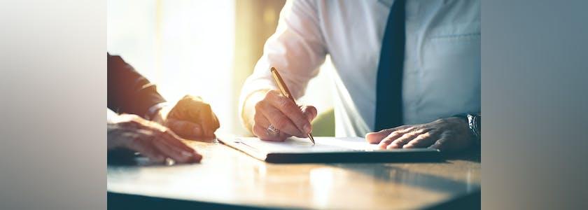 Homme signant un contrat sur une table